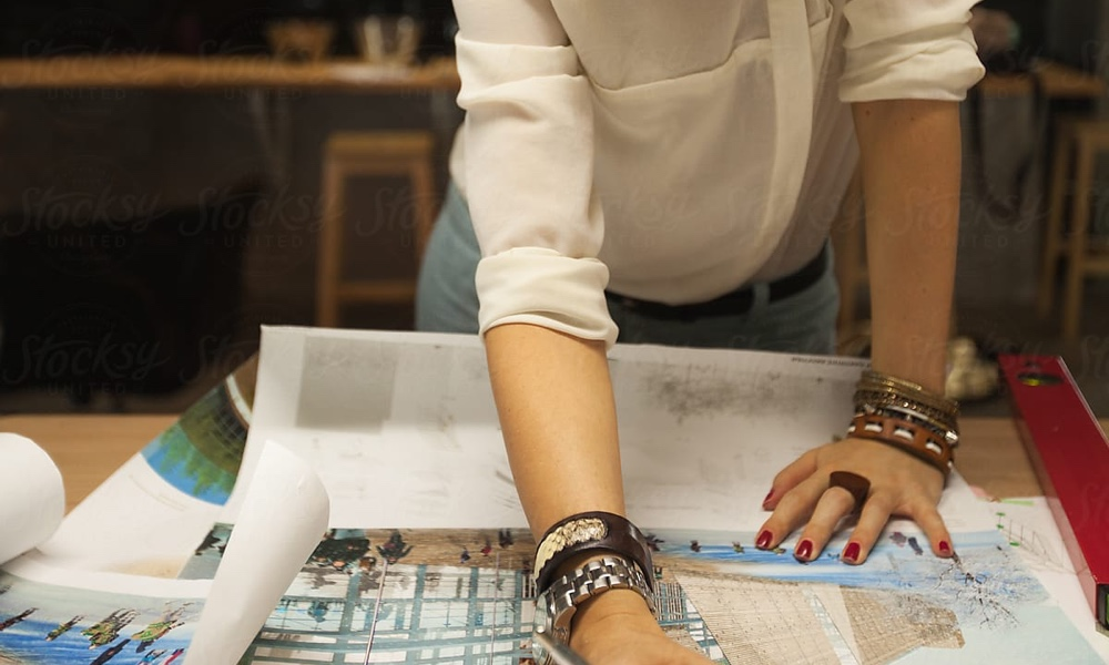 woman working on plans for hospitality design services